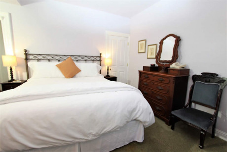 The Napa Inn - bed with white linens and dresser
