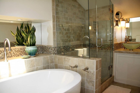 stone bathroom with soaking tub, shower and sink area